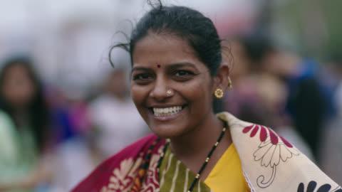 slo mo. woman smiles and laughs at camera on busy mumbai street. - indien bildbanksvideor och videomaterial från bakom kulisserna