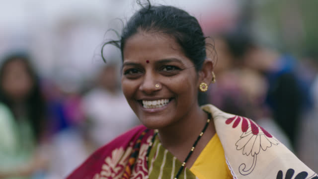 slo mo. woman smiles and laughs at camera on busy mumbai street. - india video stock e b–roll