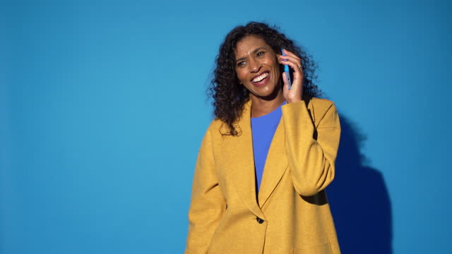 a woman smiles and laughs on the phone - coloured background stock videos & royalty-free footage