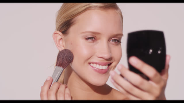 a woman smiles and uses large makeup brush on cheeks - make up stock videos and b-roll footage