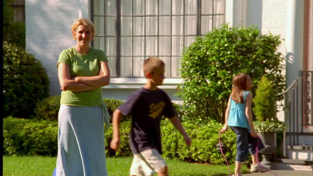 a woman smiles as children play in the suburban yard around her. - large family stock videos & royalty-free footage