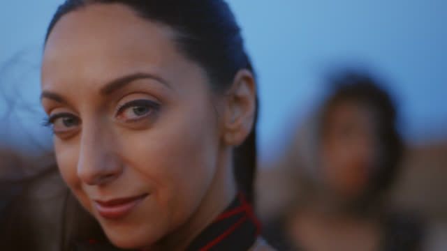 stockvideo's en b-roll-footage met cu. woman smiles at camera as wind blows her hair at magic hour. - hip