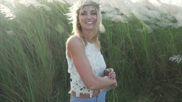 Woman smiles at camera in tall grass