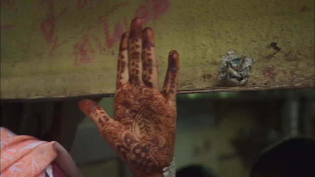 A woman smiles while she displays a traditional Mehndi tattoo on her hand. Available in HD.