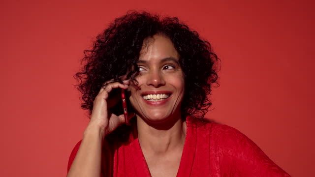 a woman smiles while talking on the phone - close up - wegsehen stock-videos und b-roll-filmmaterial
