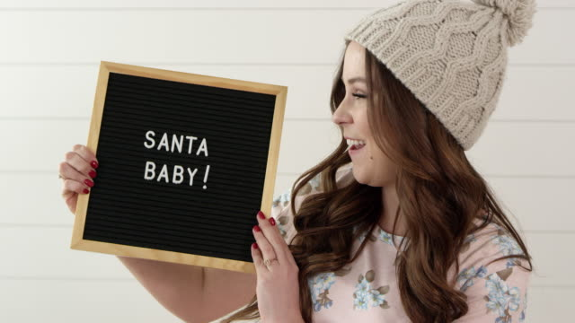 woman smiling and holding sign that says, santa baby - western script stock videos & royalty-free footage