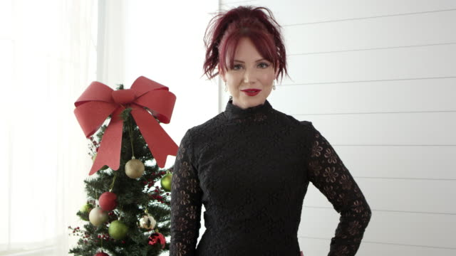 woman smiling and posing in front of small christmas tree - black dress stock videos & royalty-free footage