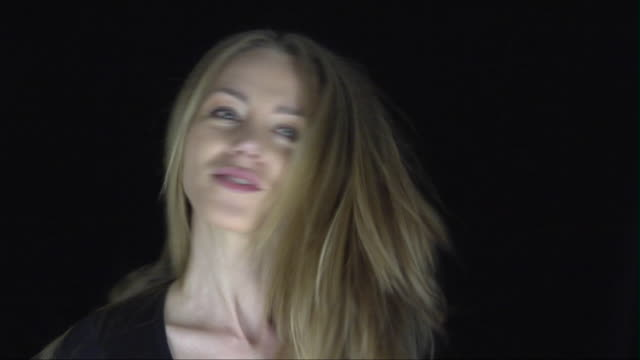 cu woman smiling and shaking long hair against black background/ rome, italy - eitelkeit stock-videos und b-roll-filmmaterial