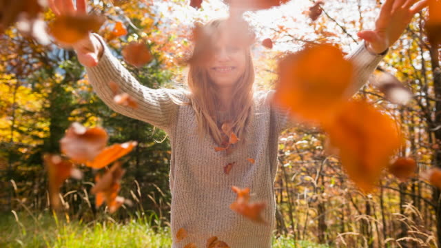 Woman smiling and throwing autumn leaves towards the camera
