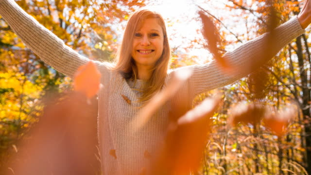 woman smiling and throwing colorful leaves towards the camera - beautiful woman stock videos & royalty-free footage