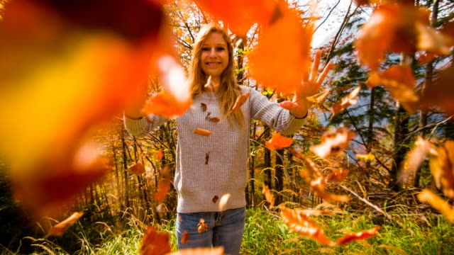 woman smiling and throwing colorful leaves towards the camera - autumn stock videos & royalty-free footage