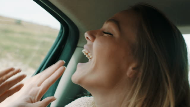 woman smiling and waving in back seat of the car - young women stock videos & royalty-free footage