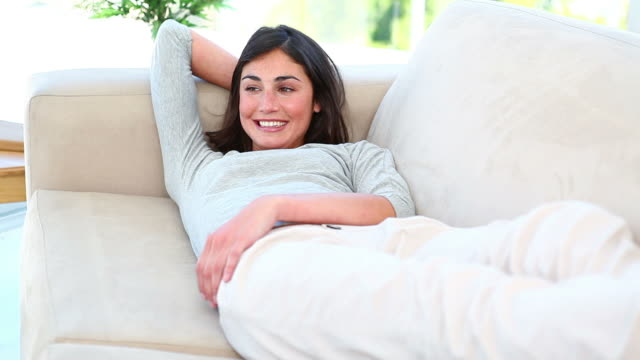 a woman lying on the couch and smiling - woman hands behind head stock videos & royalty-free footage