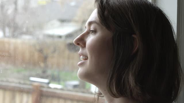 woman smiling as she looks out the window - プロボ点の映像素材/bロール