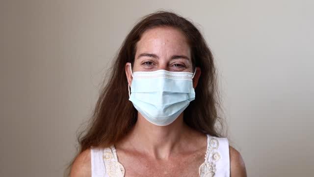 stockvideo's en b-roll-footage met woman smiling behind mask - alleen één oudere vrouw