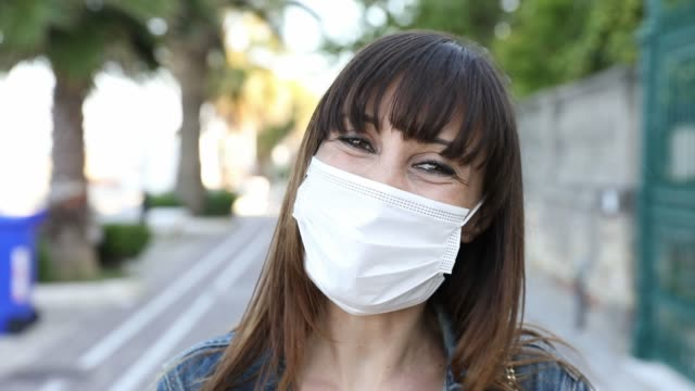 woman smiling behind the protective mask - surgical mask stock videos & royalty-free footage