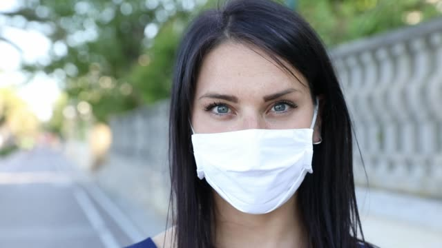woman smiling behind the protective mask - mid adult stock videos & royalty-free footage