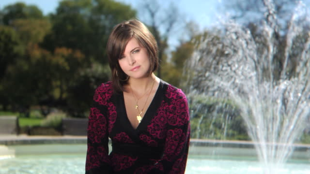 stockvideo's en b-roll-footage met hd crane: woman smiling by the fountain - crane shot
