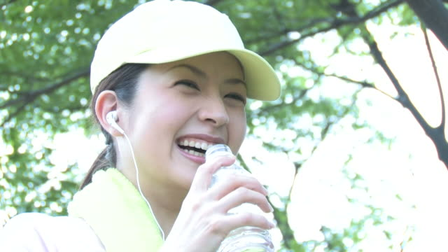 Woman smiling, holding PET bottle