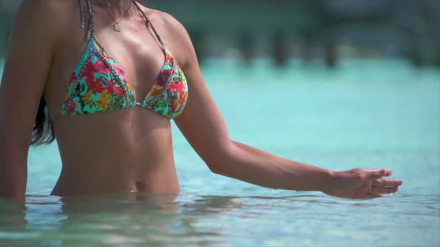 vídeos de stock, filmes e b-roll de a woman smiling in a bikini, lifestyle at a tropical island resort. - swimwear