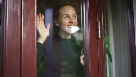 stockvideo's en b-roll-footage met de glimlachende vrouw kijkt uit venster van binnenkanthuis - waving
