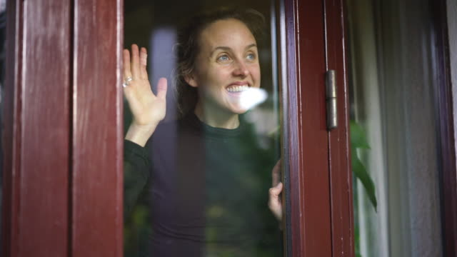 woman smiling looks out of window from inside home - waving stock videos & royalty-free footage