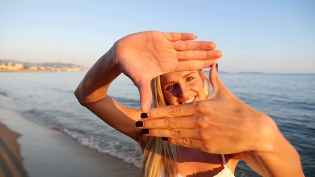 woman smiling through frame made from fingers - picture frame stock videos & royalty-free footage
