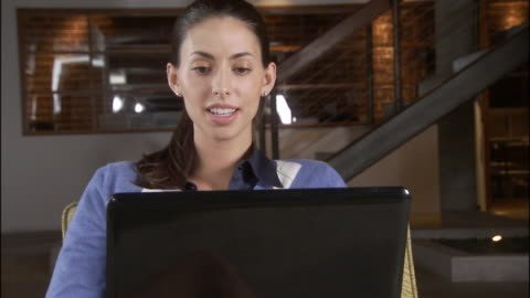 cu zo ms woman smiling while using laptop and sitting in chair in sparse office / los angeles, california, usa - 2007 stock videos & royalty-free footage