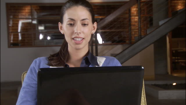 cu zo ms woman smiling while using laptop and sitting in chair in sparse office / los angeles, california, usa - haar nach hinten stock-videos und b-roll-filmmaterial