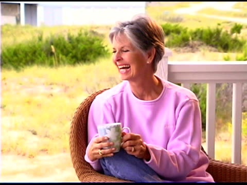 woman smiling with drink outdoors - only mature women stock videos & royalty-free footage