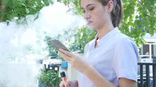 woman smoke e-cigarette and using phone