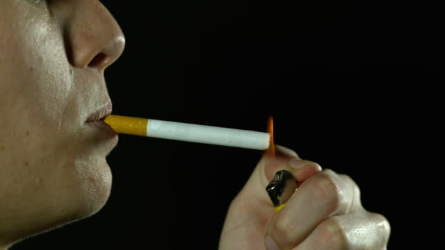 woman smoking a cigarette against black background, slow motion 4k - smoking stock-videos und b-roll-filmmaterial