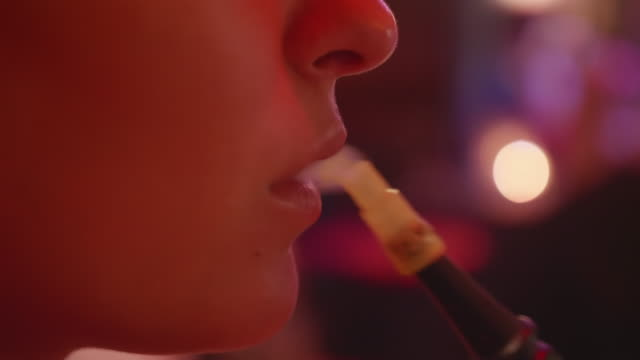 a woman smoking a hookah pipe at a lounge. - water pipe stock videos & royalty-free footage