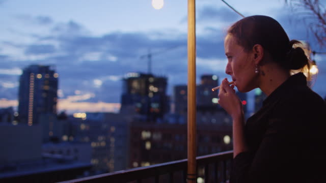 woman smoking on rooftop terrace - cigarette stock videos & royalty-free footage