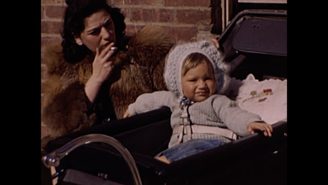 1945 woman smoking with baby in stroller / baby on mother's lap - home movie - woolly hat stock videos & royalty-free footage