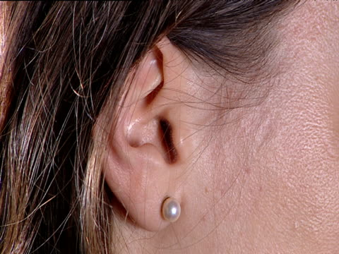 vídeos y material grabado en eventos de stock de woman smoothes hair behind ear pierced with pearl stud earring - oreja