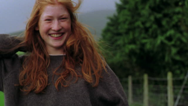 portrait woman smoothing back long red hair blowing in wind + smiling / kilkenny county, ireland - redhead stock videos & royalty-free footage