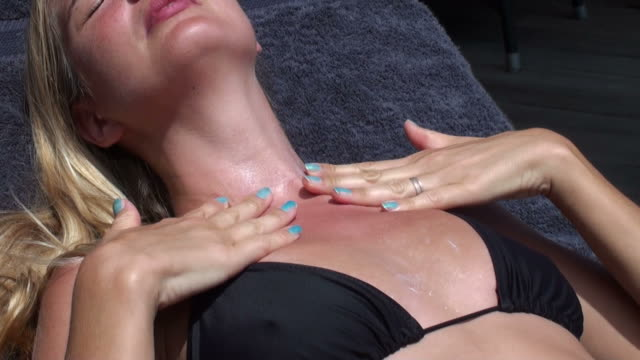 Woman smoothing suntan lotion on her reddened breast and neck