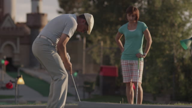 ms pan woman sneezing, distracting man preparing to hit golf ball / orem, utah, usa - golfer stock videos and b-roll footage