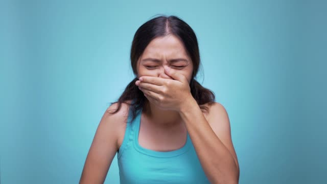 woman sneezing on isolated blue background 4k - allergy stock videos & royalty-free footage
