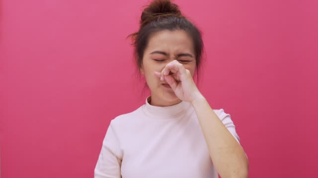 woman sneezing on isolated pink background 4k - chinese ethnicity stock videos & royalty-free footage