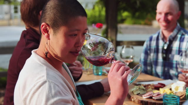 woman sniffing and swirling wine at al fresco wine tasting - slow motion - smelling stock videos and b-roll footage