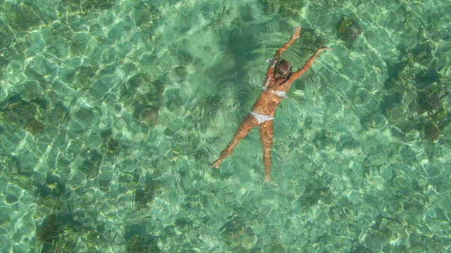 woman snorkeling swimming in a bikini at scenic tropical island in over water bungalow hotel resort, aerial drone view. - slow motion - island stock videos & royalty-free footage