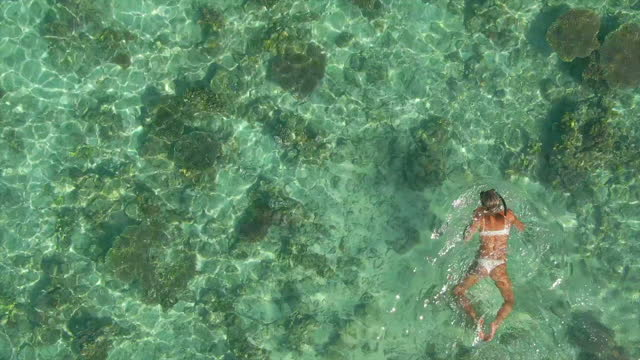 woman snorkeling swimming in a bikini at scenic tropical island in over water bungalow hotel resort, aerial drone view. - slow motion - swimwear stock videos & royalty-free footage