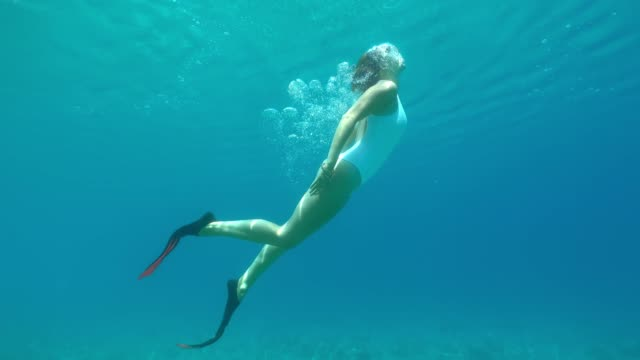 MS Woman snorkeling underwater in blue ocean