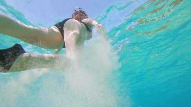 MS Woman snorkeling underwater in sunny blue ocean