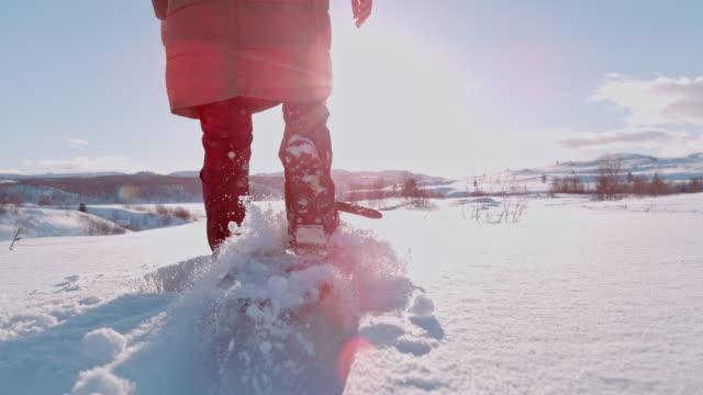 SLO MO vrouw sneeuwschoenen door de sneeuw