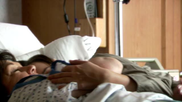 vídeos de stock, filmes e b-roll de woman snuggling in hospital bed with mature woman - condição médica