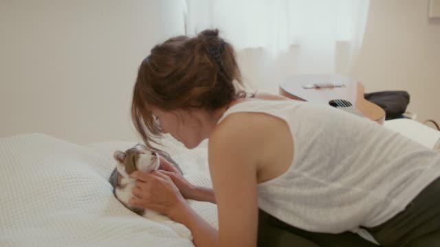 woman snuggling with cat on bed - one animal bildbanksvideor och videomaterial från bakom kulisserna