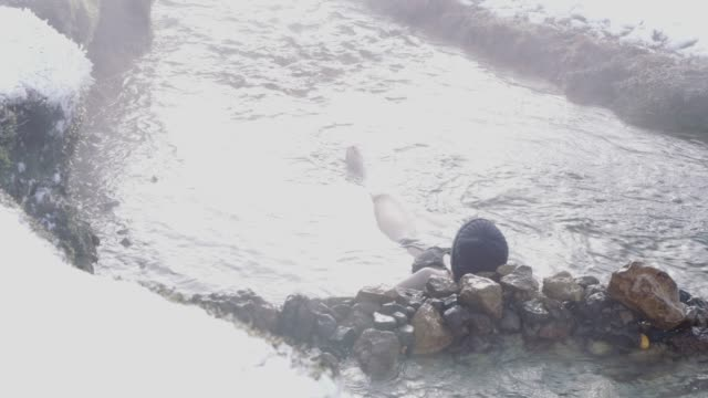vídeos de stock e filmes b-roll de ms woman soaking in steaming hot spring,iceland - só uma mulher de idade mediana